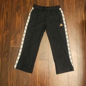 Adidas black workout  track pants with gold adidas loga on front. Size S.
